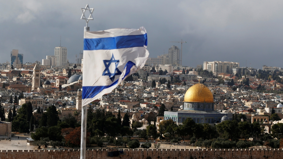 An Israeli flag is seen in the forground with the golden Dome of the Rock seen in the background.