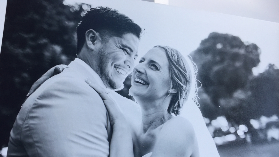 Photograph of a black and white wedding photo, bride laughing in groom's arms