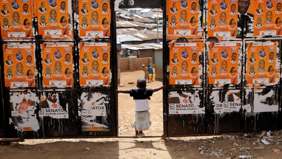 A child plays at the entrance of a polling station pasted with campaign posters ahead of the presidential election in the Kibera slums of Nairobi, Kenya.