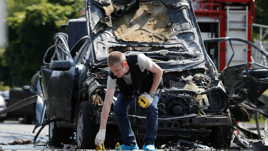 An investigator works at the scene of a car bomb explosion that killed Maksym Shapoval, a high-ranking Ukrainian official involved in military intelligence, in Kiev