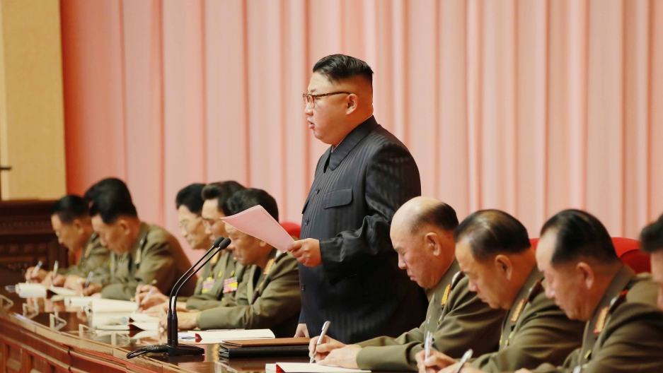 North Korean leader Kim Jong-un stands at a table in the middle of several military members .