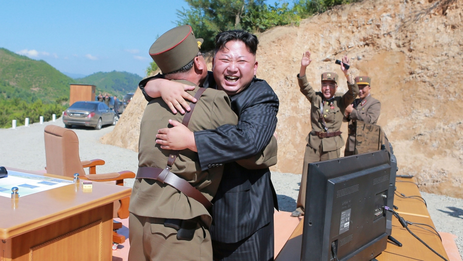 North Korean leader Kim Jong-un cheers with scientists and technicians after the test-launch of the intercontinental ballistic missile
