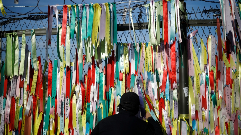 A man peeps through a barbed-wire fence with brightly color ribbons hanging from it.