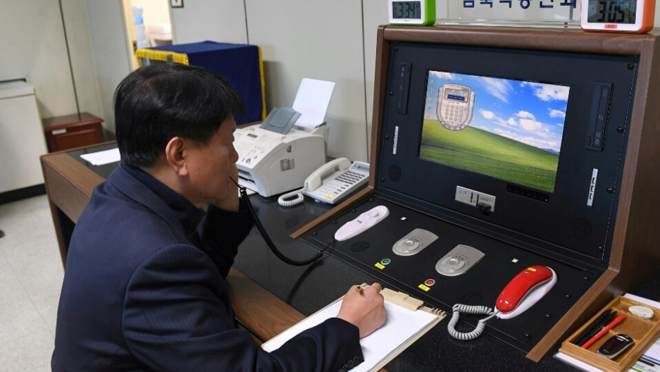 A South Korean government official sits at a terminal that has a red and green phone.
