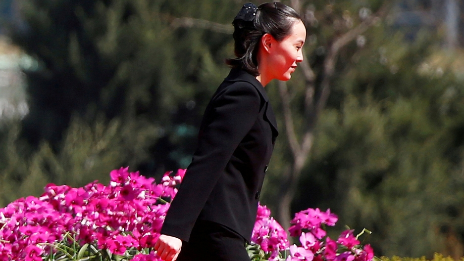 Kim Yo Jong, sister of North Korean leader Kim Jong-un, walks past a flowering bush weaing a black pants suit.
