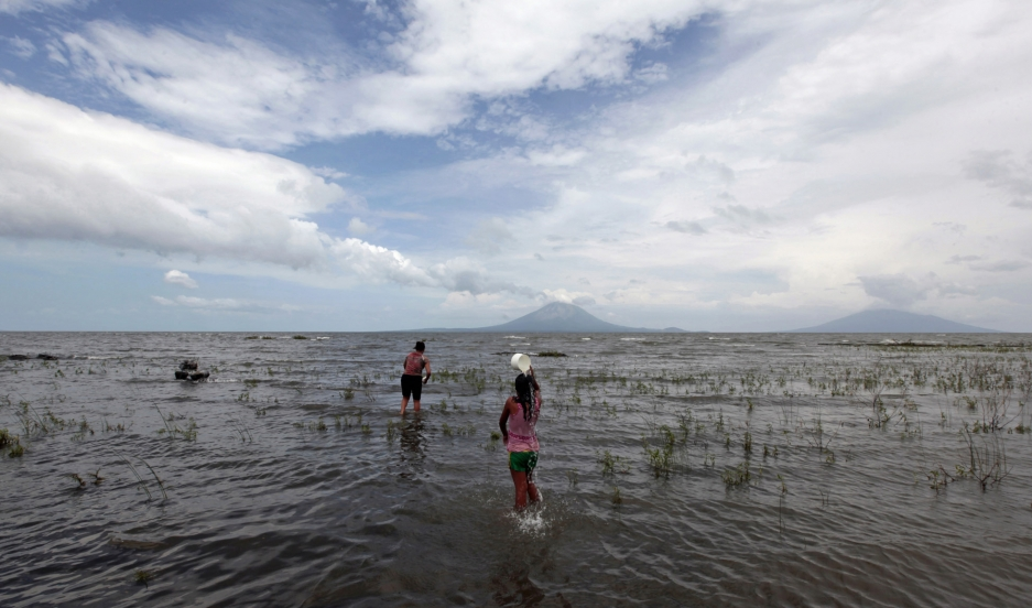 Local residents wade into the shallow waters of Lake Nicaragua, the largest in Central America, with the volcanic island of Ometepe in the distance. Many are worried that the lake will be contaminated by the country's new $50 billion Chinese-backed Pacifi