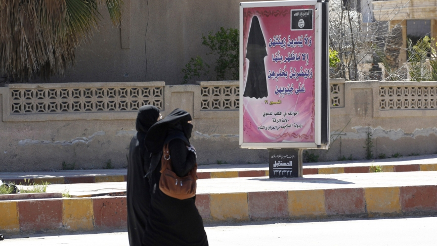 A billboard displays a verse from the Koran that urges women to wear a hijab in the northern province of Raqqa in March. ISIS has imposed sweeping restrictions like this in areas where it has gained control.