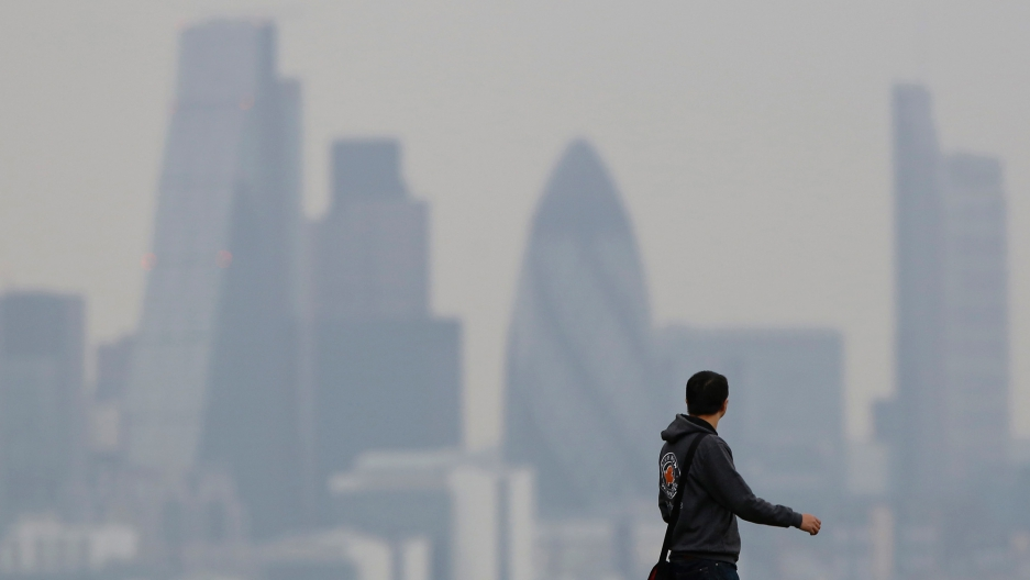 A man walks through Greenwich Park as a haze of pollution sits over the London skyline.