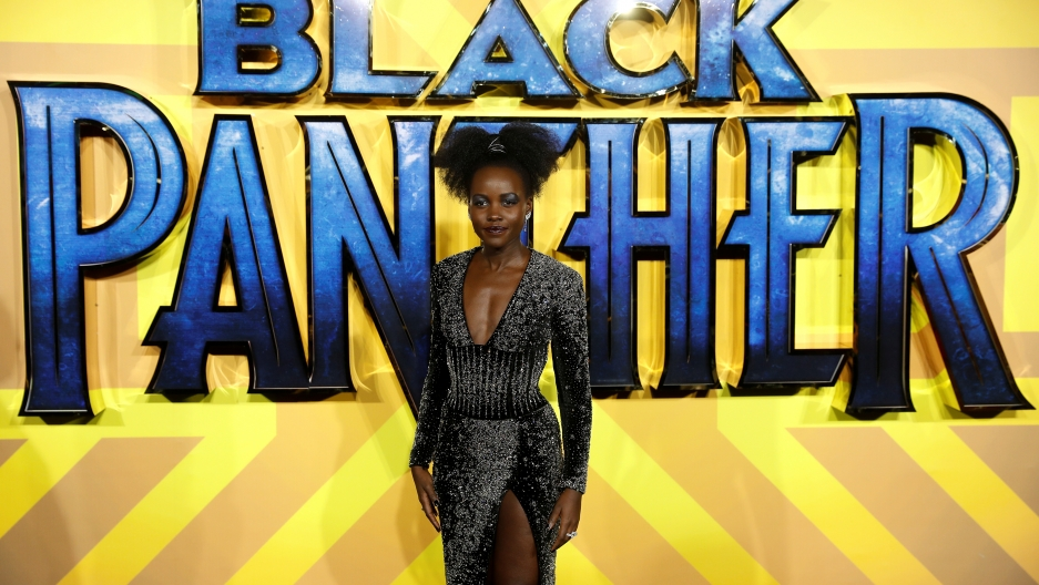Actor Lupita Nyong'o posing in front of a giant Black Panther backdrop