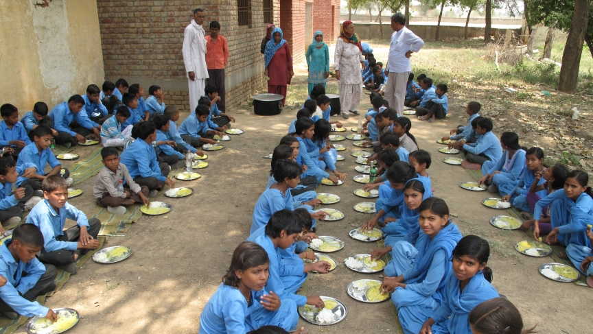 Schoolchildren in Haryana, India eat rice and kadhi, a curry made with onions, garlic, yogurt and fritters made with chick pea flour.