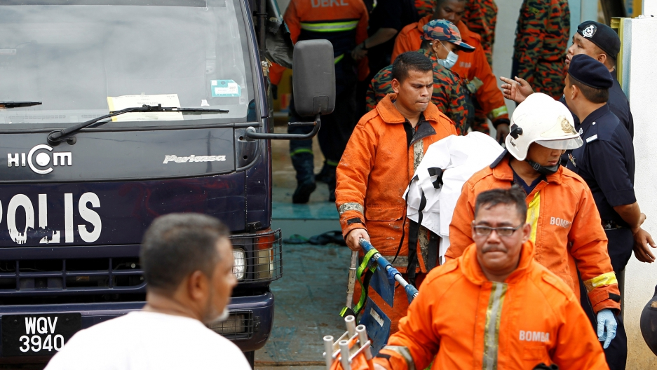 Firefighters leave religious school Darul Quran Ittifaqiyah after a fire broke out in Kuala Lumpur, Malaysia.
