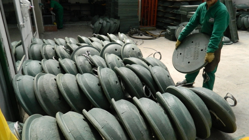 A worker at Maderplast in Bogota stacks plastic manhole covers.  They're designed to replace the thousands of metal covers that thieves have been stealing to sell as scrap metal.