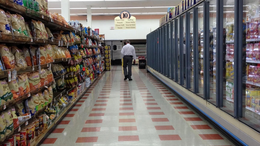 Michael Dunleavy walks down an empty aisle of the Market Basket grocery store he manages in Somerville, Mass.