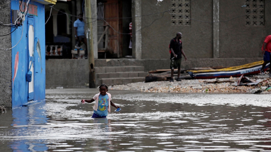 A girl trudges through a flooded area after Hurricane Matthew in Les Cayes, Haiti.