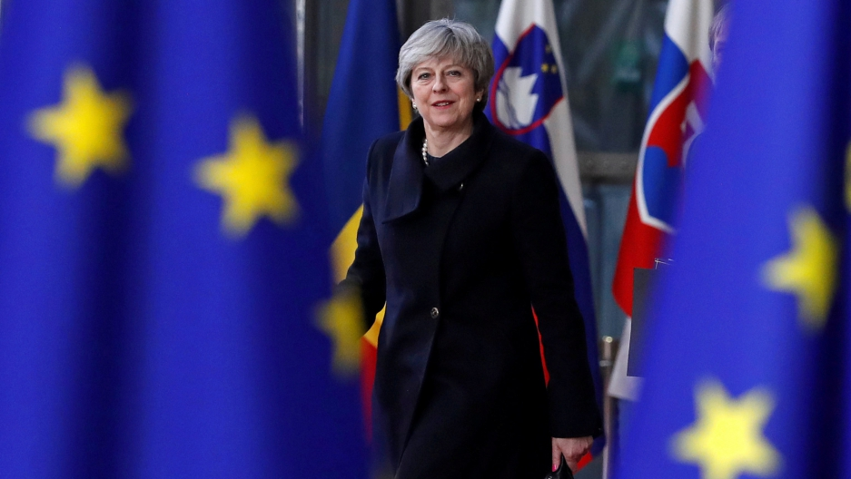 Britain's Prime Minister Theresa May wearing a dark blue jacket is picture between two EU flags in the foreground.