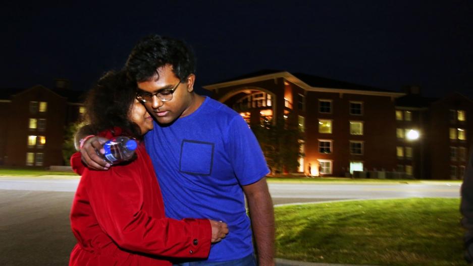 Woman hugs man in evening scene in front of building
