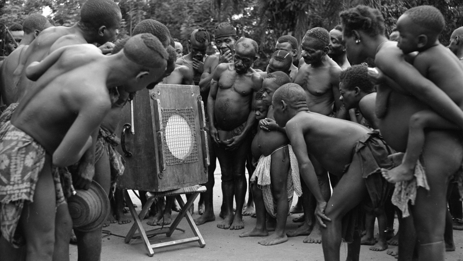 A group of Mbuti Pygmies listen to playback of their own music in the Democratic Republic of Congo in 1952. The recording was made by ethnomusicologist Hugh Tracey.