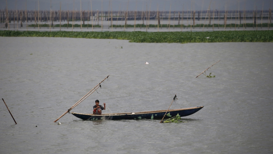 A resident fishes in the waters near Manila, Philippines, amid heavy current and winds brought by Typhoon Melor in some parts of the country. Wide areas of the central Philippines were plunged into darkness on Tuesday as Melor barreled into the coconut-gr