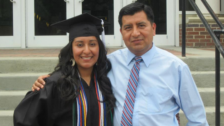 Portrait of woman in graduation cap and gown with man whose are is around her shoulder