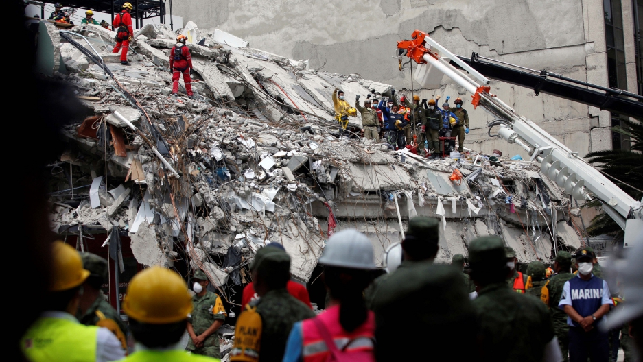 Members of Israeli and Mexican rescue teams gesture for a minute of silence after retrieving a dead body from a collapsed building after an earthquake in Mexico City, Mexico, on Sept. 21, 2017.