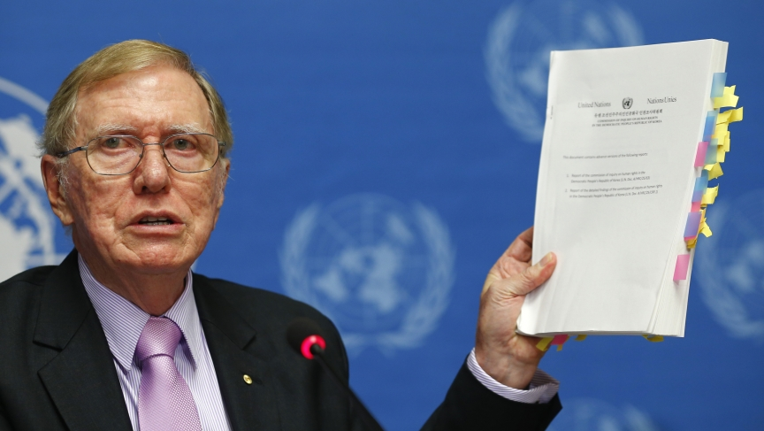 Michael Kirby, chairperson of the Commission of Inquiry on Human Rights in North Korea holds a copy of his report during a news conference at the United Nations in Geneva February 17, 2014.