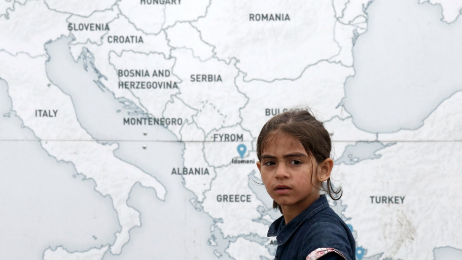 A girl walks past a map illustrating part of Europe, at a makeshift camp for refugees and migrants at the Greek-Macedonian border in Greece.