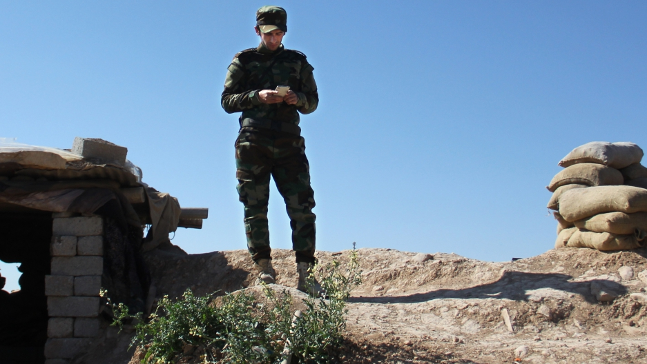 A Kurdish-Iraqi fighter checking his smart photo on the frontline outside Erbil, in Kurdistan.