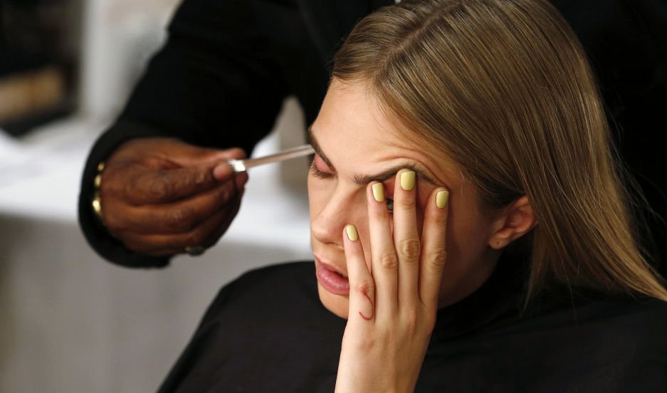 Model Cara Delevingne has her hair styled backstage during London Fashion Week.