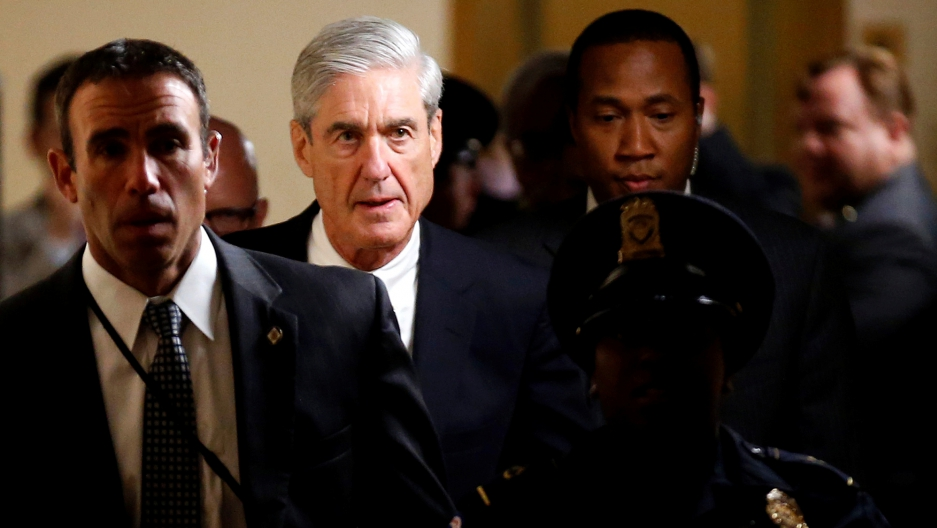 Special Counsel Robert Mueller is shown walking down a hallway surrounded by staff and police.