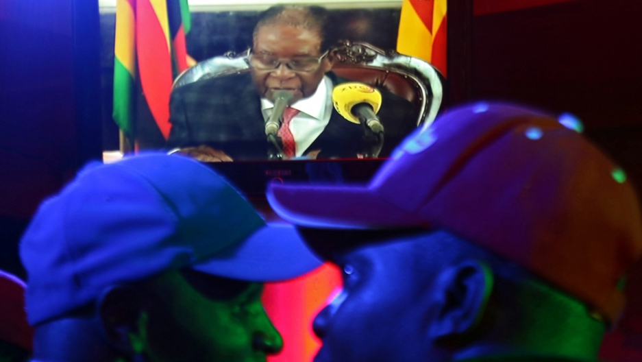 Two men in the foreground wearing baseball hats watch Zimbabwean President Robert Mugabe on a TV.