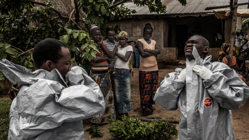 Members of a Red Cross burial team put on personal protective equipment before entering the home of a woman suspected of dying of Ebola in the village of Dia on Monday, August 18, 2014.