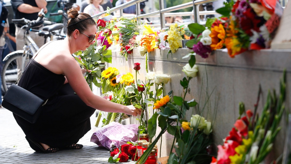 A women places flowers near the Olympia shopping mall, where Friday's shooting rampage started, in Munich.