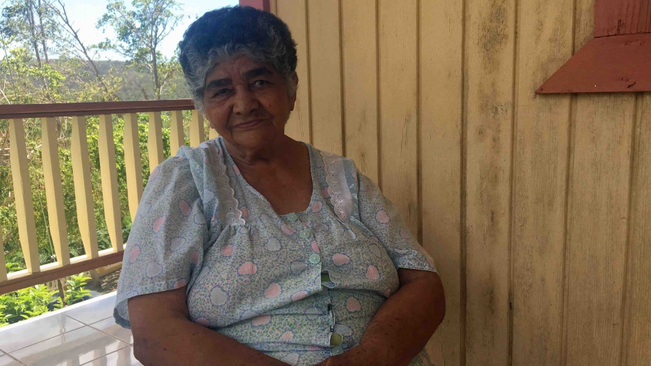 An elderly woman sitting on a porch.