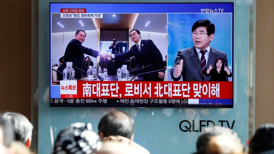 People watch a TV broadcasting a news report on a high-level talks between the two Koreas at the truce village of Panmunjom, in Seoul, South Korea, Jan. 9, 2018.