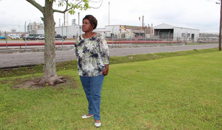 Margie Richard stands in what used to be her front yard, across the street from Shell's chemical plant in Norco, Louisiana. Richard pushed for the company to buy out the neighborhood and move residents.