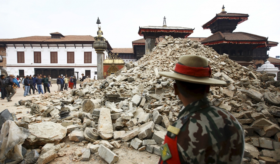 A Nepalese army personnel stands in front of a collapsed temple in Bhaktapur, Nepal a day after the April 25 earthquake rocked the country. The quake devastated the heavily crowded Kathmandu valley, killing thousands and triggering a deadly avalanche on M