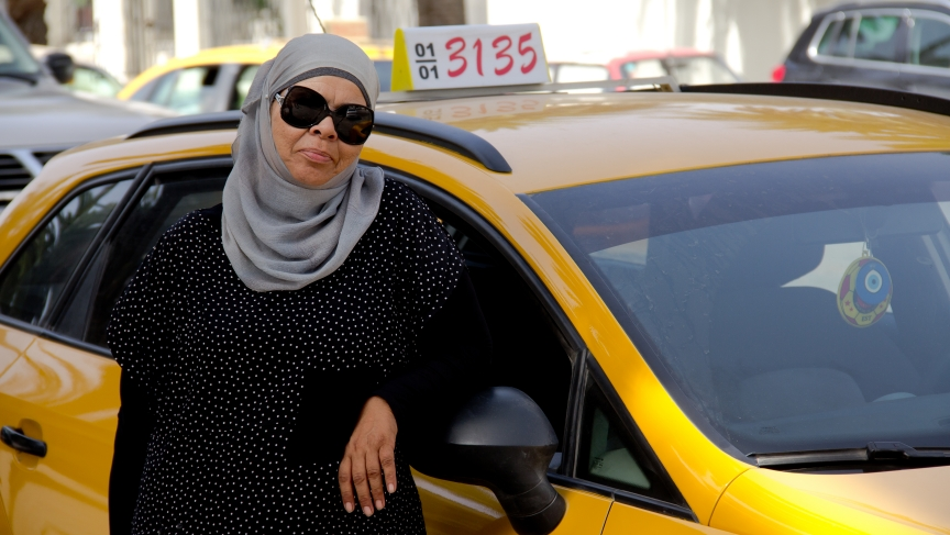 Yamina Jaouani in front of the cab that her daughter helped her buy. She's been driving a taxi in Tunis for nearly 30 years.
