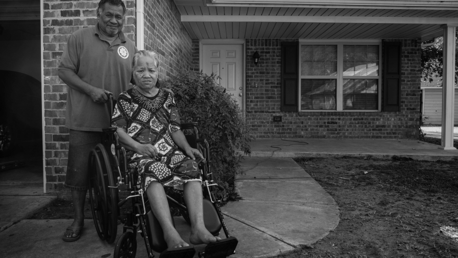 black and white photo of man and woman in wheelchair in front of house