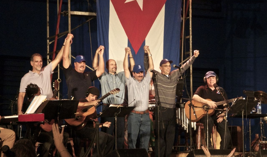 "The ""Cuban Five,"" a group of five intelligence officers recently returned to Cuba in an exchange with the United States, celebrate on stage with musical artist Silvio Rodriguez."