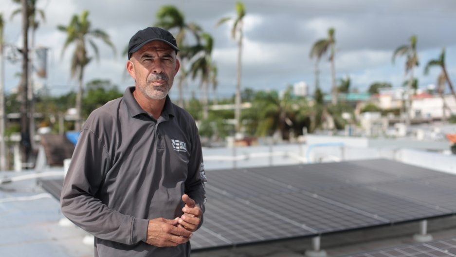 Technician Alexis Portalatin stands next to rooftop solar panels he is connecting to a new Tesla battery storage system the San Juan suburb of Guaynabo. The storage system will allow the panels to operate separately from the power grid and supply electric