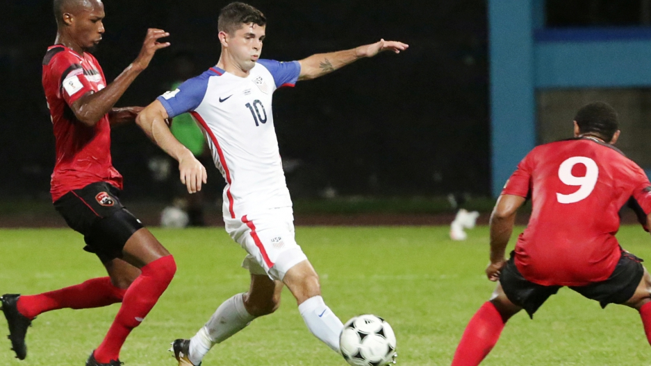United States' Christian Pulisic and Trinidad's Kevan George and Shahdon Winchester in action.