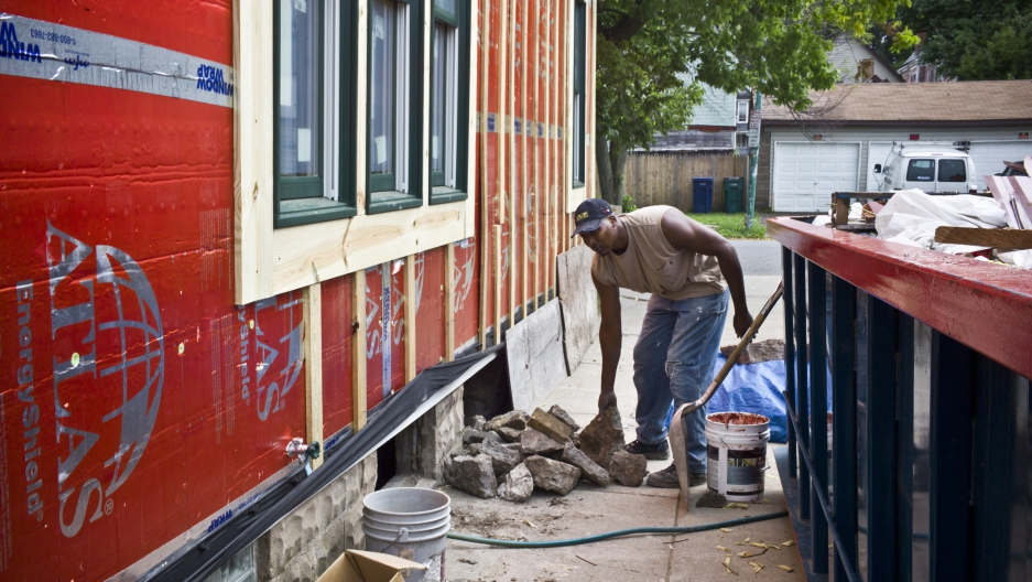A worker with the community organization PUSH Buffalo weatherizes a home on Buffalo's lower west side. The formerly vacant home was completely rehabbed — with solar panels and other-energy efficient features — and is now rented to a low-income family.