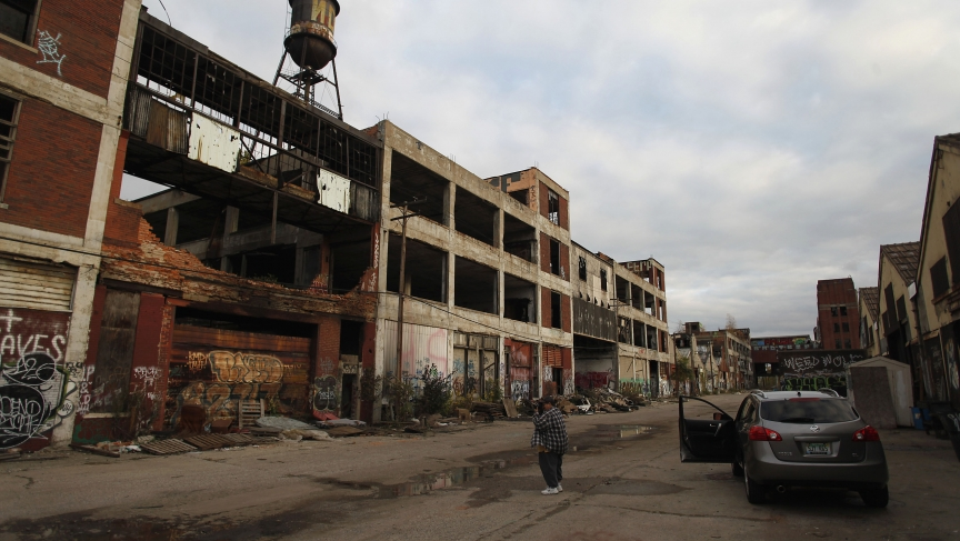 A man takes a picture of deteriorating buildings at the former Packard plant in Detroit, Michigan.