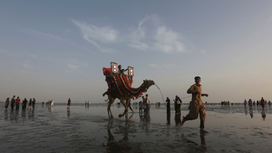A man leads a camel with children taking a ride on it along the Clifton beach in Karachi, Pakistan