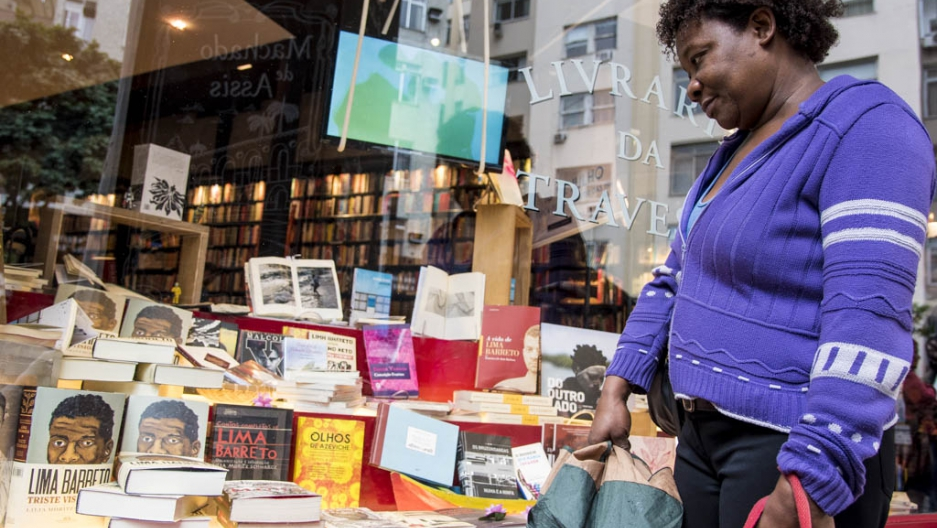A woman in Brazil surveys a diverse display of books in a bookshop