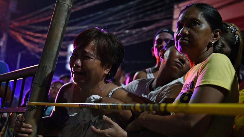 A relative of a victim cries behind the police line at the site of a recent drug-related shooting by unidentified men riding on motorcycles in Manila.
