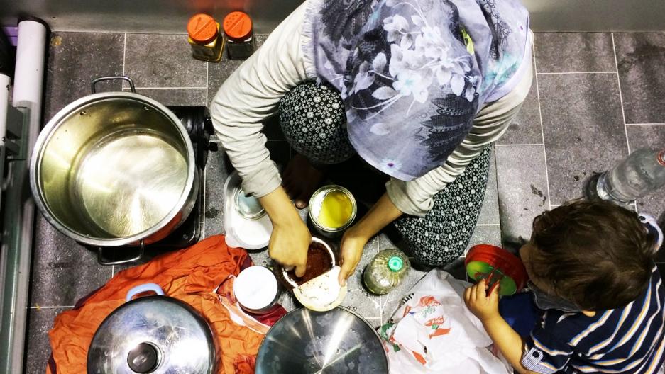 Bushra cooks food for her family inside her temporary living quarters at Berlin's Tempelhof refugee shelter.