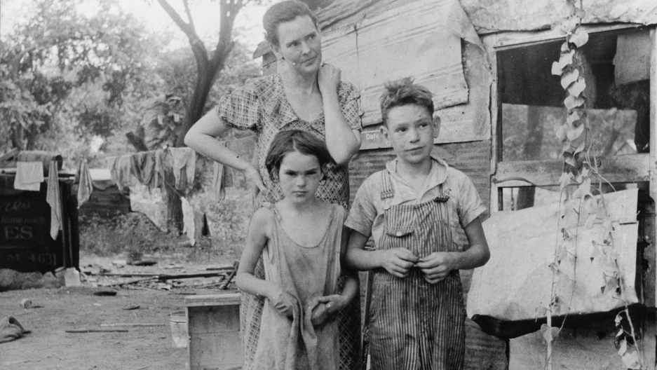 The Great Depression pushed millions of Americans into catastrophic poverty. Here, a mother and her shoeless children stand beside their home, a tin shack, in Elm Grove, Oklahoma, 1st August 1936