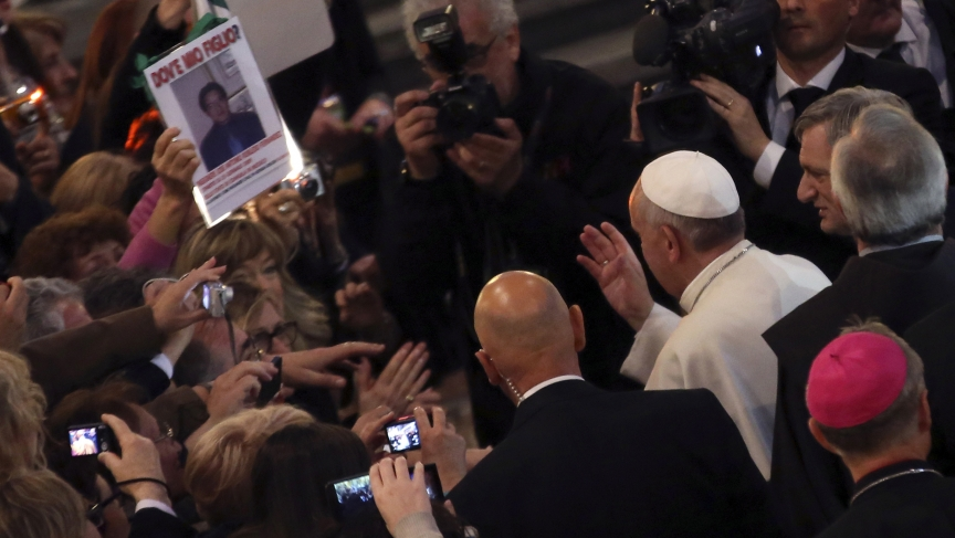 "Pope Francis waves to faithful as he arrives to lead an audience with the family members of victims of the mafia at the San Gregorio VII church in Rome. A woman shows a picture of her son with the words, ""Where is my son?"""