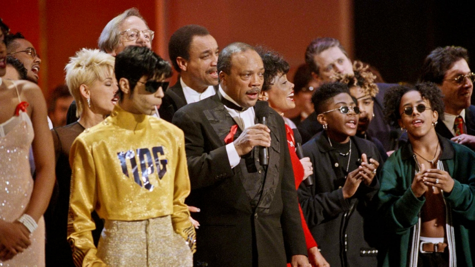 Prince, next to Quincy Jones, wearing gold pants and a shiny yellow shirt